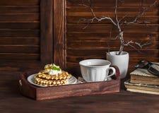 Galletas con la miel y la crema y té con el limón en una bandeja de madera del vintage en una tabla de madera oscura Libros, vidr Imagen de archivo libre de regalías