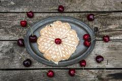 Galletas con las cerezas en la placa, madera Imagen de archivo libre de regalías