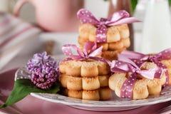Galletas con las cintas rosadas en un milksha blanco de la placa y del chocolate Foto de archivo libre de regalías
