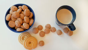 Galletas de almendra en un florero en las galletas de la tabla y una taza de café Foto de archivo libre de regalías