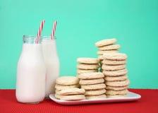Galletas de azúcar apiladas en la placa con las botellas de leche Imágenes de archivo libres de regalías