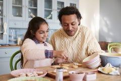 Galletas de And Daughter Decorating del padre en casa junto imagen de archivo