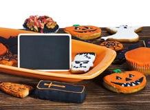 Galletas de Halloween y muestra negra para el texto congratulatorio Imagen de archivo libre de regalías