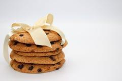 Galletas de harina de avena con las gotas de chocolate, atadas con una cinta de oro, aislada en el fondo blanco fotografía de archivo