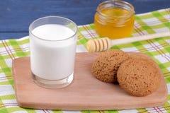 Galletas de harina de avena con leche y miel en un tablero en una tabla de madera azul fotografía de archivo libre de regalías
