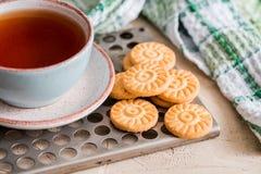 Galletas de harina de avena hechas en casa con una taza de té en viejo fondo de madera Fotos de archivo
