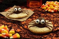 Galletas de la araña de Halloween en fondo anaranjado y negro Foto de archivo libre de regalías