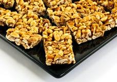 Galletas de la barra de cacahuete en la placa negra Imagen de archivo