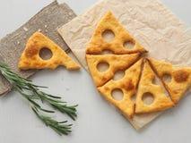 Galletas de la forma de la rebanada del queso sobre el pergamino con el tronco del romero foto de archivo