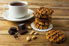 Galletas de la formación de hielo del chocolate y taza de té Imagen de archivo