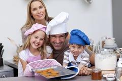 Galletas de la hornada de la familia en la cocina Fotografía de archivo libre de regalías