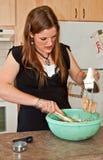 Galletas de la hornada de la mujer joven con el mezclador Imagen de archivo libre de regalías