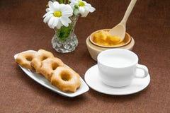 Galletas de la miel, taza y un florero de margaritas Fotografía de archivo