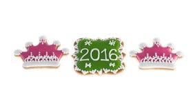 Galletas 2016 de la Navidad con dos coronas rosadas en el fondo blanco Foto de archivo libre de regalías