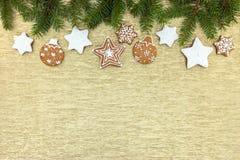 Galletas de la Navidad con las ramas blancas de la formación de hielo y del abeto en el oro Imágenes de archivo libres de regalías