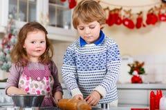 Galletas de la Navidad de la hornada del muchacho y de la muchacha en casa Imagen de archivo libre de regalías