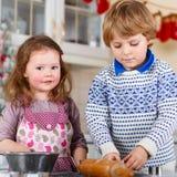 Galletas de la Navidad de la hornada del muchacho y de la muchacha en casa Imagenes de archivo