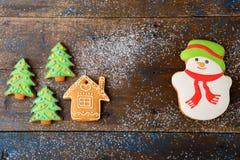 Galletas de la Navidad en la forma del muñeco de nieve, de la casa y del árbol del Año Nuevo Imagenes de archivo