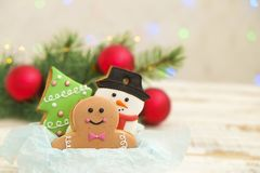 Galletas de la Navidad en una caja con los regalos, las luces y las ramas del abeto en la tabla de madera del vintage blanco Efec Imagenes de archivo