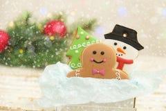 Galletas de la Navidad en una caja con los regalos, las luces y las ramas del abeto en la tabla de madera del vintage blanco Efec Foto de archivo libre de regalías