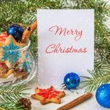 Galletas de la Navidad y del Año Nuevo Tarjeta de la Feliz Navidad con nieve Imagenes de archivo