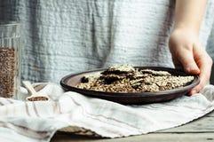 Galletas de la semilla de lino, del sésamo, del girasol y de las especias, manos Foto de archivo