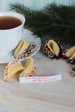 Galletas de la suerte y una taza de té en la tabla Imágenes de archivo libres de regalías