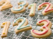Galletas de la torta dulce del número con la formación de hielo Foto de archivo libre de regalías