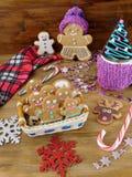 Galletas de los hombres de pan de jengibre en una cesta de mimbre rodeada por las decoraciones de la Navidad Fotos de archivo libres de regalías