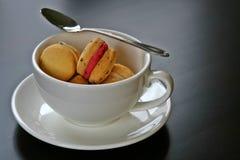 Galletas de los macarrones en una taza Imagen de archivo