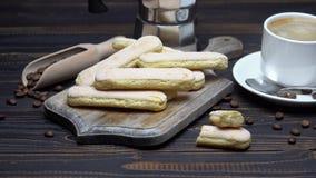 Galletas de los melindres de Savoiardi del italiano y taza de café en fondo de madera almacen de video