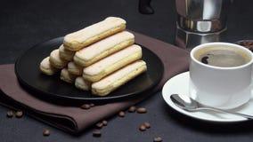 Galletas de los melindres de Savoiardi del italiano y taza de caf? en fondo concreto metrajes