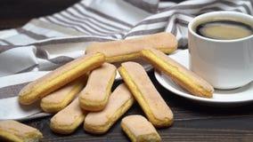 Galletas de los melindres de Savoiardi del italiano y taza de caf? en fondo de madera almacen de video