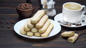 Galletas de los melindres de Savoiardi del italiano y taza de caf? en fondo de madera almacen de metraje de vídeo