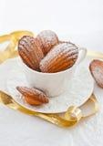 Galletas de Madeleines en una taza blanca Imagen de archivo libre de regalías