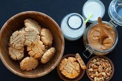 Galletas de mantequilla de cacahuete con leche en un fondo negro imagen de archivo