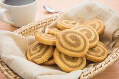 Galletas de mantequilla en cesta de mimbre y taza de café Foto de archivo