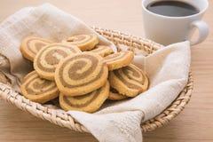 Galletas de mantequilla en la cesta de mimbre y la taza de café, imagen filtrada Fotografía de archivo