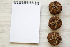 Galletas de microprocesador de chocolate con el cuaderno en una tabla de madera blanca, desde arriba Imagenes de archivo