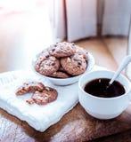 Galletas de microprocesador de chocolate en servilleta y té caliente en la tabla de madera Imagen de archivo libre de regalías