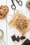 Galletas de microprocesador de chocolate hechas en casa con la leche, fondo de madera blanco rústico Fotos de archivo
