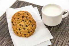 Galletas de microprocesador de chocolate y taza de leche Imágenes de archivo libres de regalías