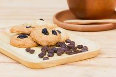 Galletas de pasa con la semilla seca del café en la tabla de madera con c marrón Fotos de archivo