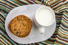 Galletas de pasa de la harina de avena y taza de leche Fotografía de archivo libre de regalías