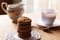 Galletas de pasa hechas en casa de la harina de avena con la taza de café en de madera Fotos de archivo libres de regalías