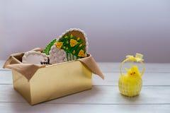 Galletas de Pascua en una caja en fondo de madera gris Fotos de archivo