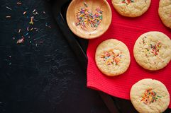 Galletas de torta dulce con confeti en una servilleta roja en un ston negro Foto de archivo