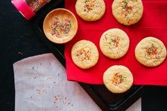 Galletas de torta dulce con confeti en una servilleta roja en un ston negro Imagenes de archivo