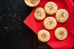 Galletas de torta dulce con confeti en una servilleta roja en un ston negro Foto de archivo libre de regalías