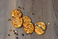 Galletas de torta dulce en una tabla de madera con las nueces y los granos de café fotos de archivo libres de regalías